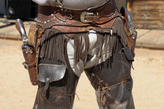 Wild West Gunfighter. Cowboy gunfighter sports guns, holster and chaps Royalty Free Stock Photos