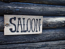 Wild west saloon sign. Wild west American saloon sign hanged on a wooden house Stock Photography
