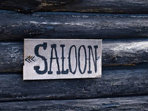 Wild west saloon sign. Wild west American saloon sign hanged on a wooden house Royalty Free Stock Photography