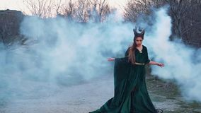 Wild witch in long free flying green emerald dress stands in thick white fog and raises her hands, a lady calls a