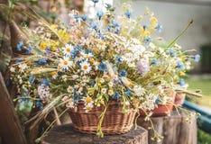Wilde Bloemen in een Mand op een Rustieke Achtergrond Stock Afbeelding