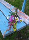 Wilde Blumen auf Bank Stockfoto