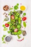 Wilde kruidensalade met tomaten, olijven, olie en azijn op witte houten achtergrond royalty-vrije stock afbeelding