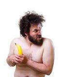 Wilde mens die verward een banaan bekijken Stock Foto