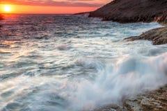 Wilde overzees onder een vurige oranje zonsondergang Stock Foto's