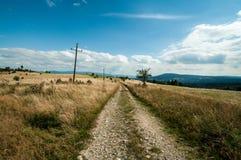 Wilde rotsachtige weg onder berggebieden. Stock Foto