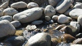 Wilde waterstromen door de keien stock footage