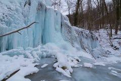 Wilder Fluss, schöne gefrorene Wasserfälle und frischer Schnee in einem Gebirgswald, an einem kalten Wintertag Lizenzfreie Stockbilder
