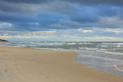 Wilder sandiger Strand unter bewölktem Himmel des Sonnenuntergangs Lizenzfreies Stockbild