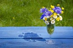 Wilder Sommer blüht im Weinglas auf blauer alter Tabelle stockbild