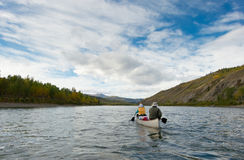Wilderness adventure canoeists paddle Pelly River. A couple of canoeists on wilderness adventure trip paddling wide Pelly River, central Yukon Territory, Canada Stock Photography