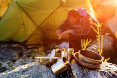 Wilderness explorer camping. Adventure camping man cooking alone outdoors with tent, sunrise and lens flare in the mountain morning sunlight. Happy explorer Stock Photos