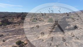 Wilderness scenery with a clock. Digital composite of a rocky plain with little vegetation. Analogue clock is running in the foreground stock footage