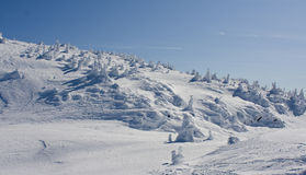 Wilderness Winter Terrain. High alpine scenery showing windswept snow across rocky mountain top Royalty Free Stock Photo