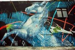 Wildes Pferd durch unbekannten Künstler auf rustikaler Straßenwand mit Graffiti Lizenzfreie Stockfotos
