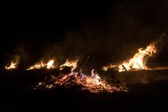 Wildfire burning on grass and wood at night. dangerous place on fire. close-up fire shot. Wildfire burning on grass and wood at night. dangerous place on fire royalty free stock photo