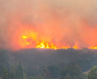 Wildfire burning out of control. Large wildfire burning in the hills with a lot of smoke and high flames royalty free stock images