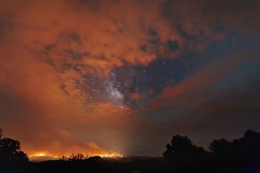 Wildfire and Milky Way. A wildfire burns in the Davis Mountains in Texas, while the clouds part and the Milky Way peeks through royalty free stock image
