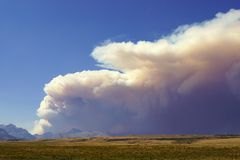 Wildfire over the Plains. Wildfire is a constant reminder of how nature renews its' self.  Here, a smoke plume drifts from a fire in the Rocky Mountain Front out Stock Image
