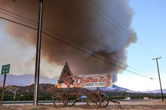 Xmas trees sign in background of the Thomas Fire in Ventura. A wildfire is an uncontrolled fire that is wiping out large fields and areas of land. Vintage royalty free stock images