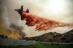 Wildfire Water Dropping Plane. An emergency water dropping plane dumps flame retardant onto a California wildfire royalty free stock photo