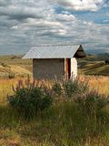 Wildflower Outhouse. A cement cinder block outhouse with a tin roof.  It is out in the Okanogan Highlands Prairie among the wild grasses and wildflowers Royalty Free Stock Images