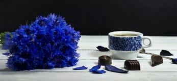 Wildflowers azuis com uma xícara de café e os doces Imagem de Stock Royalty Free