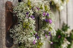 Wildflowers blancos y púrpuras hermosos en una guirnalda en la pared de madera Imagen de archivo libre de regalías