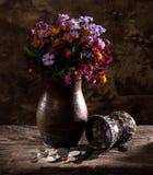 Wildflowers brillantes en florero y monedas viejas Fotos de archivo