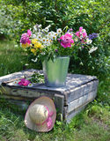 Wildflowers in a bucket with pink hat by old table Stock Photography