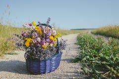 Wildflowers dans le panier Un bouquet de différentes fleurs dans le panier sur une route de champ toned Photo stock