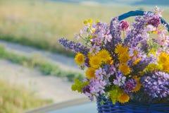 Wildflowers dans le panier Un bouquet de différentes fleurs dans le panier sur une route de champ toned Image libre de droits