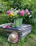 Wildflowers en un cubo con el sombrero rosado por la tabla vieja Fotografía de archivo