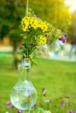 Wildflowers in a glass vase. Decorative jewelry Stock Photography