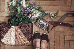 Wildflowers hermosos en mujer de mimbre del bolso y de la cámara y del inconformista Fotografía de archivo