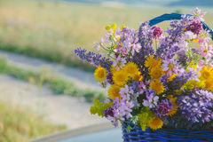 Wildflowers im Korb Ein Blumenstrauß von verschiedenen Blumen im Korb auf einem Feldweg getont Lizenzfreies Stockbild