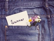 Wildflowers and paper note with the word SUMMER. Wildflowers, paper note with the word SUMMER on the background of a jeans pocket. Close-up, top view. Beautiful royalty free stock image