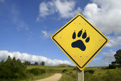 Wildlife animal concept with paw icon on road sign Stock Photography