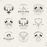 Wildlife hunters logo set. Wildlife hunters, hipster logo set with deer antlers, axe and mountains Stock Image