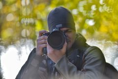 Wildlife, nature man photographer in camouflage outfit shooting,. Taking pictures Stock Photo