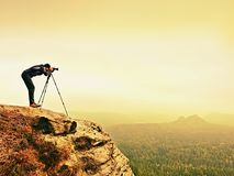Wildlife photographer on mountain summit works. Man like to travel and photography, taking pictures Stock Photography