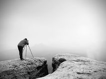 Wildlife photographer on mountain summit works. Man like to travel and photography, taking pictures Stock Images