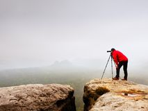 Wildlife photographer on mountain summit works. Man like to travel and photography, taking pictures Stock Image