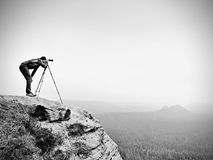 Wildlife photographer on mountain summit works. Man like to travel and photography, taking pictures. Of moments during autumnal sunset in landscape Royalty Free Stock Image