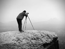 Wildlife photographer on mountain summit works. Man like to travel and photography, taking pictures Royalty Free Stock Image