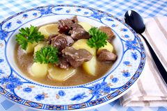 Wildsch goulash with potato, sauce on blue plate Royalty Free Stock Photos