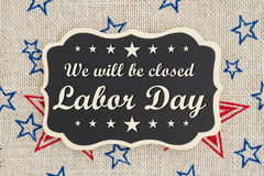 We will be closed Labor Day message. We will be closed Labor Day text on a chalkboard with patriotic USA red and blue stars on burlap stock photo