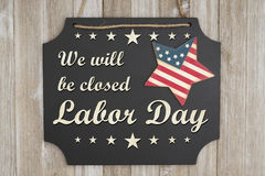 We will be closed Labor Day message. We will be closed Labor Day text on a chalkboard with patriotic USA red and blue star on weathered wood stock photography