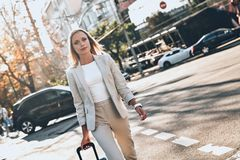 She will be in time. Beautiful young woman in suit pulling luggage while walking outdoors royalty free stock photos