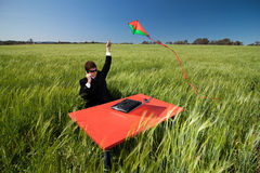 Will this business idea fly?. Businessman wondering if his idea will fly. Man in suit at desk in field flying a kite, representing his latest idea stock photography